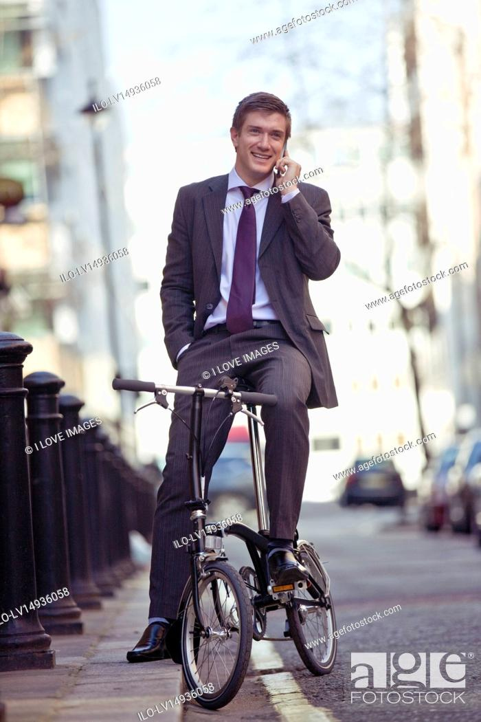 Stock Photo: A businessman on his bicycle, talking on a mobile phone.