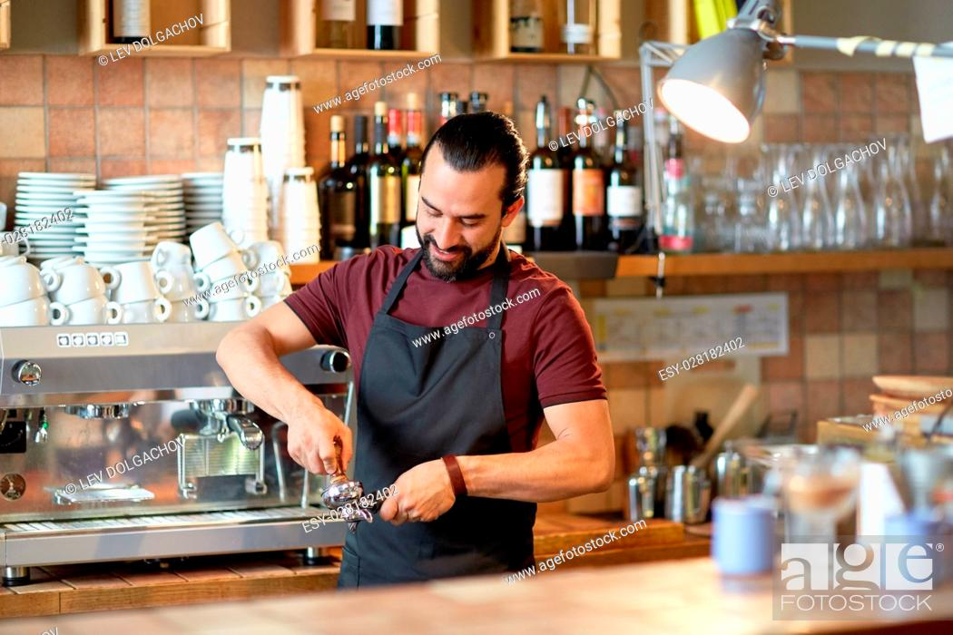 Stock Photo: small business, people and service concept - happy man or waiter in apron with holder and tamper preparing espresso at coffee shop.