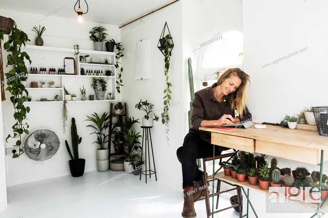 Stock Photo: Female owner of plant shop sitting at table, working on digital tablet, a selection of plants on wooden shelves.