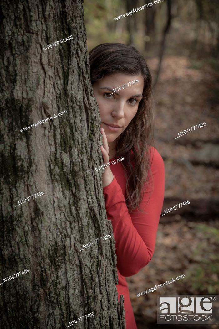 Stock Photo: Young woman in a red dress standing behind a tree in the woods during autumn.