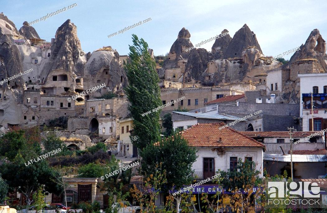 Stock Photo: Tufa cave dwellings in rock face. Jagged rock formations. Modern houses.