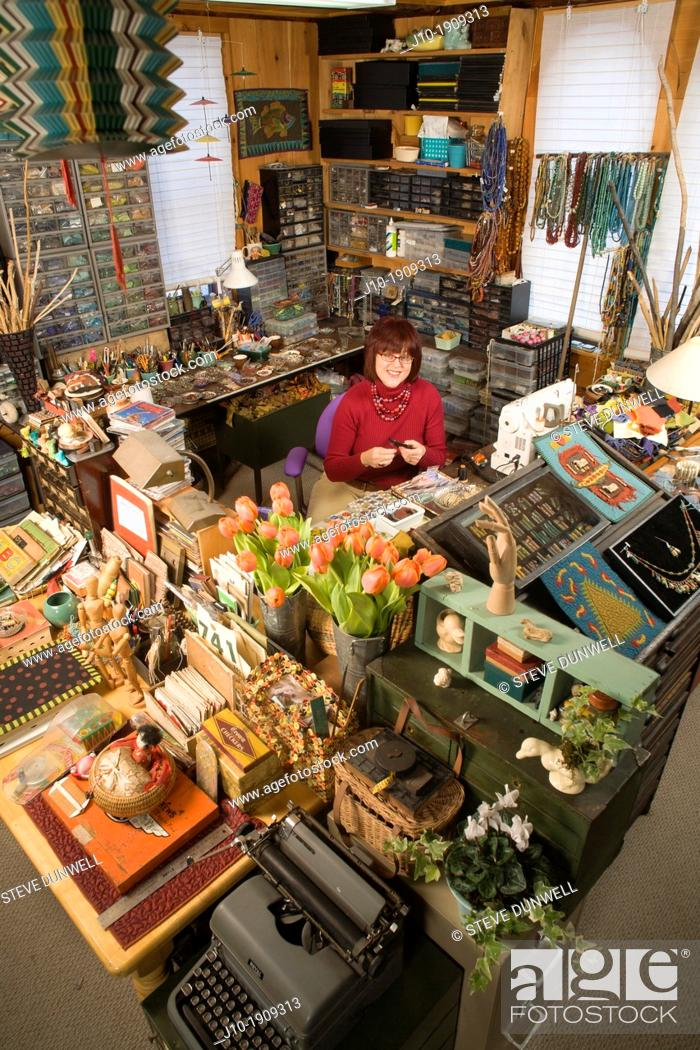 Stock Photo: artist craft person in her studio, Keene, NH working with beads and thread and bone, small business, home office.