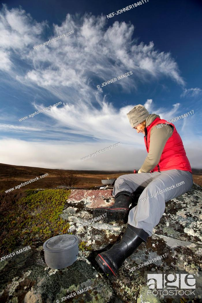 Photo de stock: Woman preparing food outdoors.