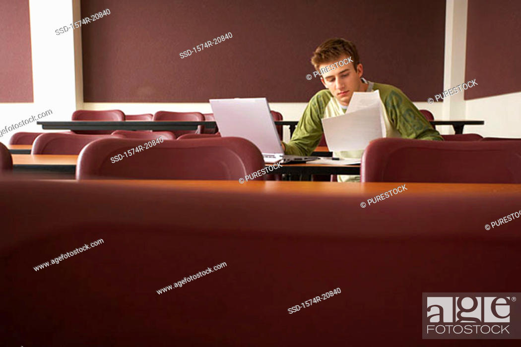 Stock Photo: College student sitting in a lecture hall and studying.
