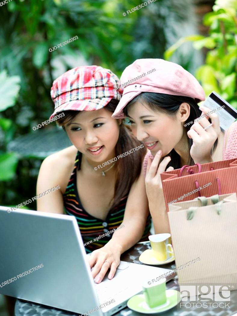 Stock Photo: Two women on outdoor patio with credit card and laptop.