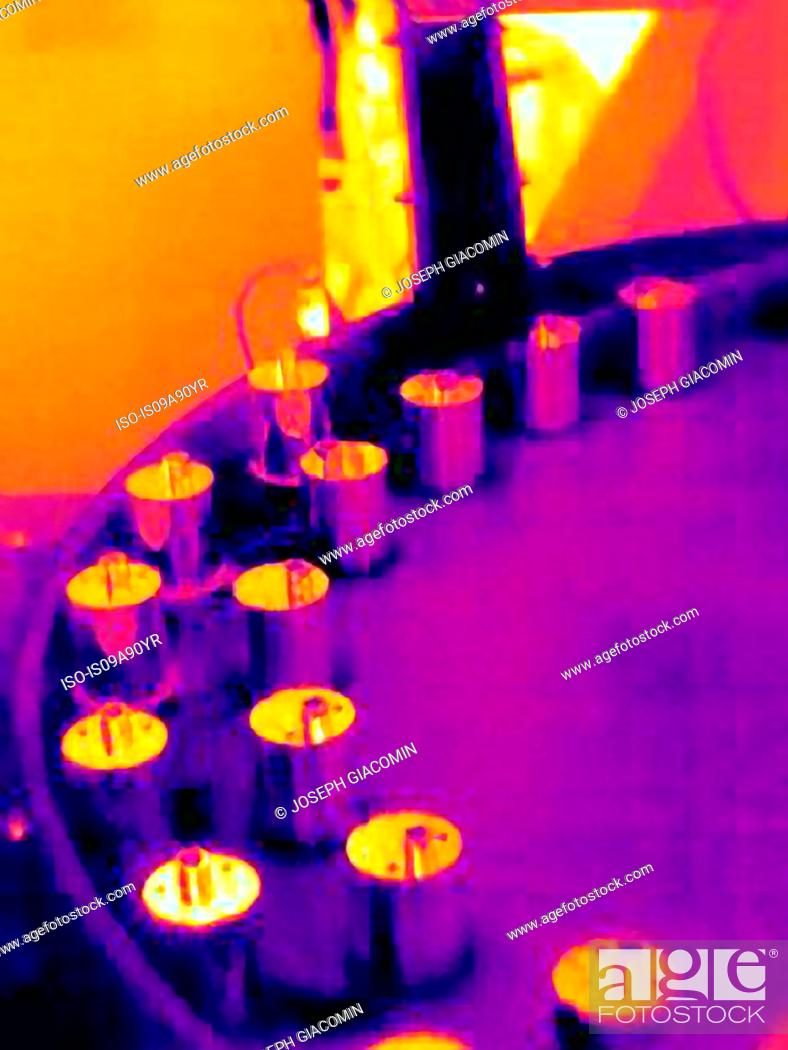 Stock Photo: Thermal image of hot machined parts emerging from a CNC machine.