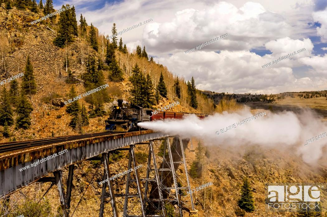 Stock Photo: The Cumbres & Toltec Scenic Railroad train pulled by a steam locomotive crosses the Cascade Trestle (over Cascade Creek) on the 64 mile run between Antonito.