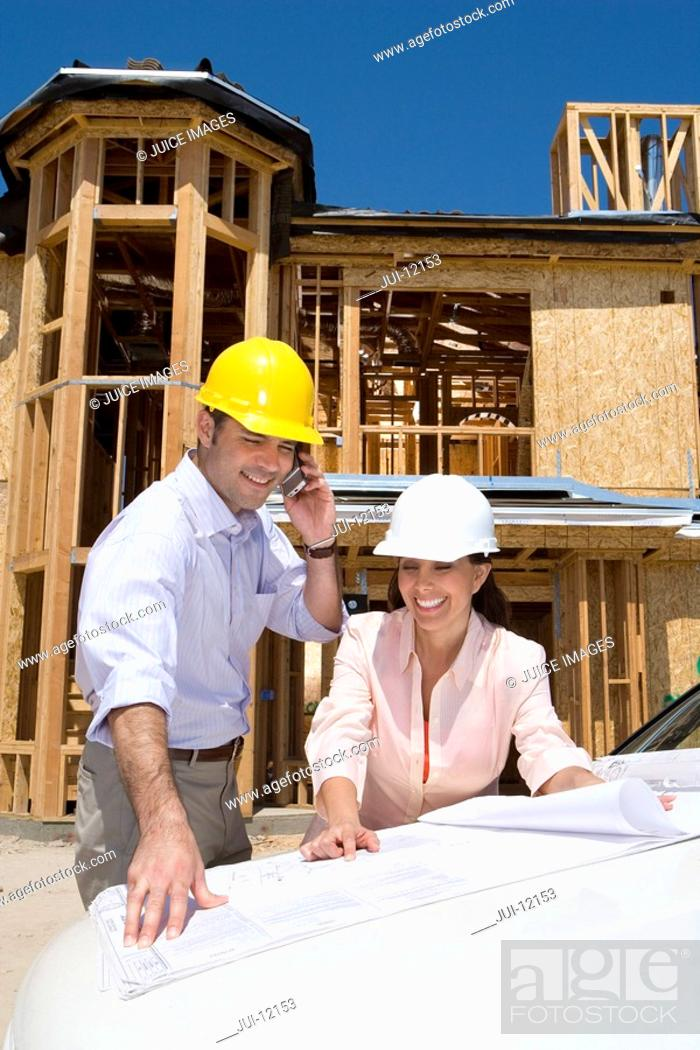 Stock Photo: Man and woman in hardhats looking at blueprint by partially built house, man on mobile phone.