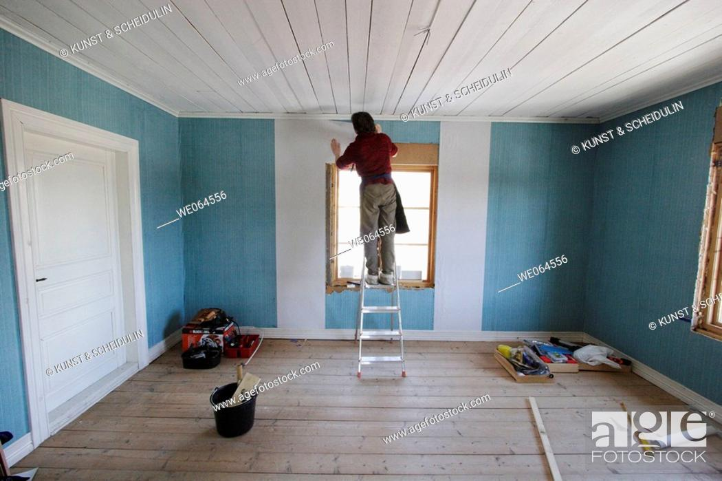Stock Photo: Woman repapering a room. Paperhanger, wallpaper, renovation. Sweden, Scandinavia, Europe.
