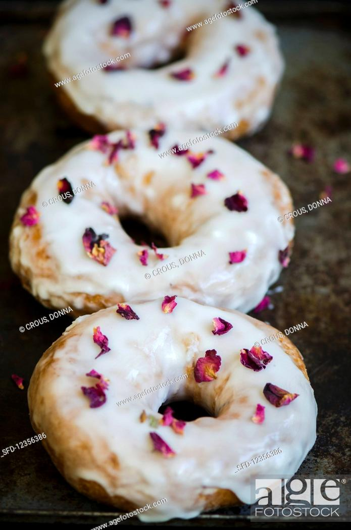 Stock Photo: Three doughnuts sprinkled with dried rose petals.