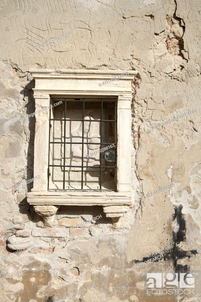 Stock Photo: Exterior of worn building with enclosed sculpture of religious theme in Venice, Italy.