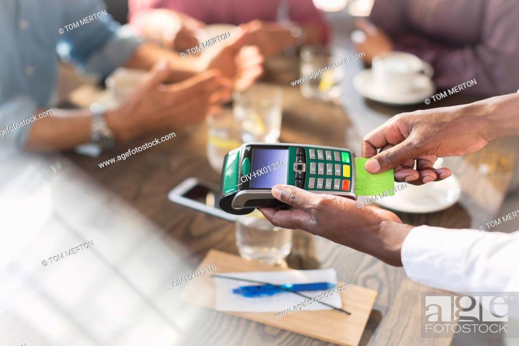 Stock Photo: Waiter using credit card reader at restaurant table.