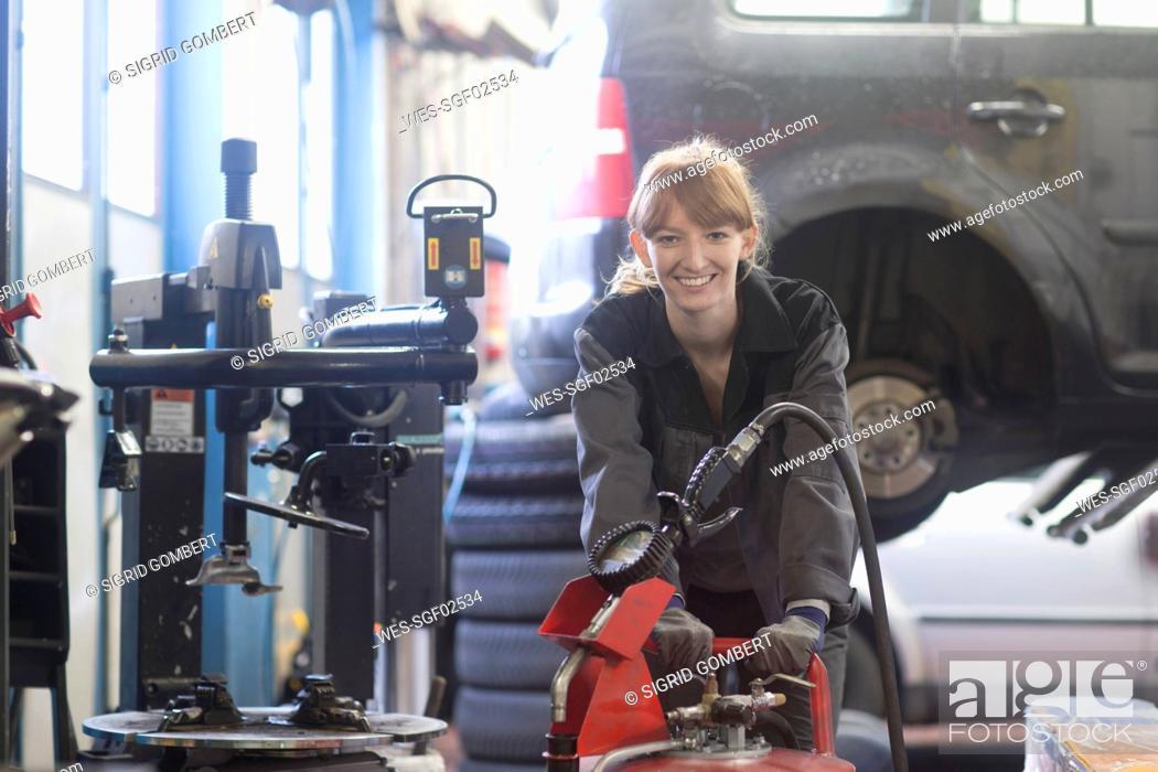 Stock Photo: Female car mechanic working in repair garage.
