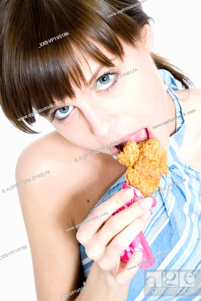 Stock Photo: young woman eating chicken nuggets.