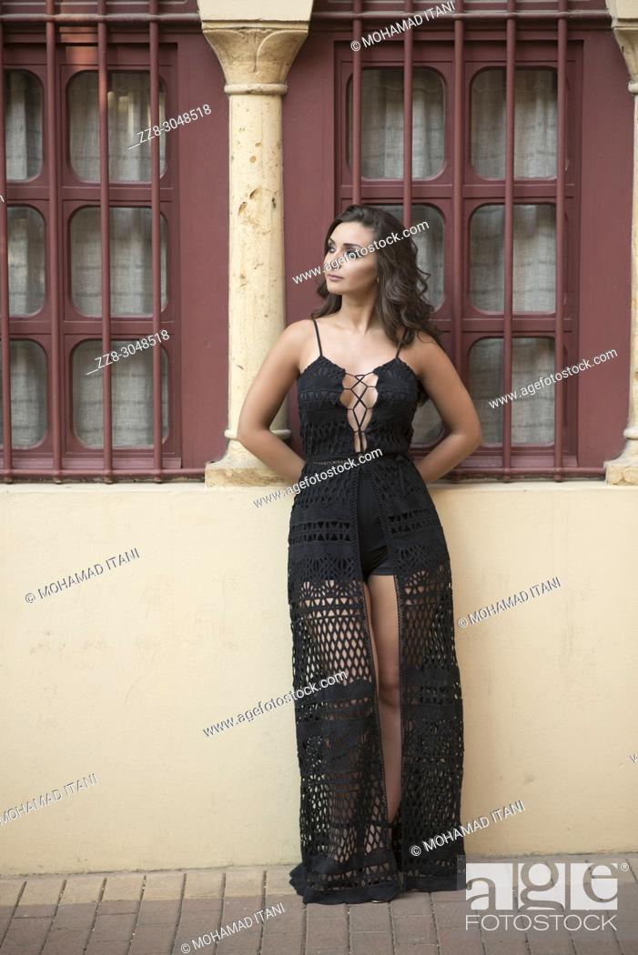 Stock Photo: Beautiful young woman wearing a asexy black dress standing outside a house looking away.