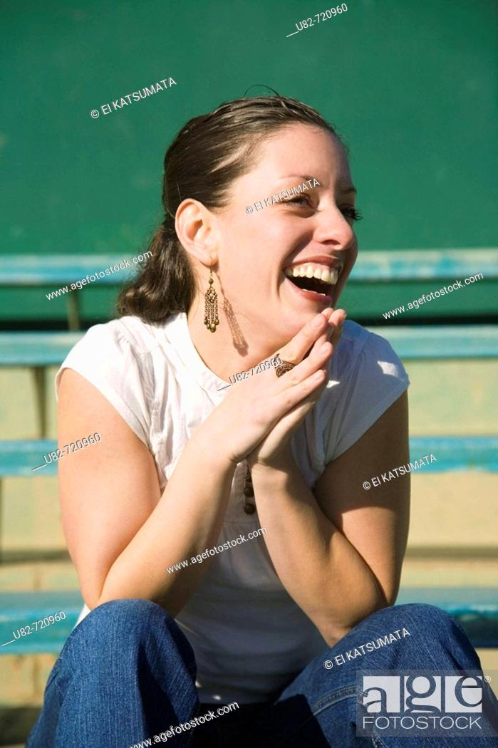 Stock Photo: Woman sitting in bleachers at a baseball stadium.