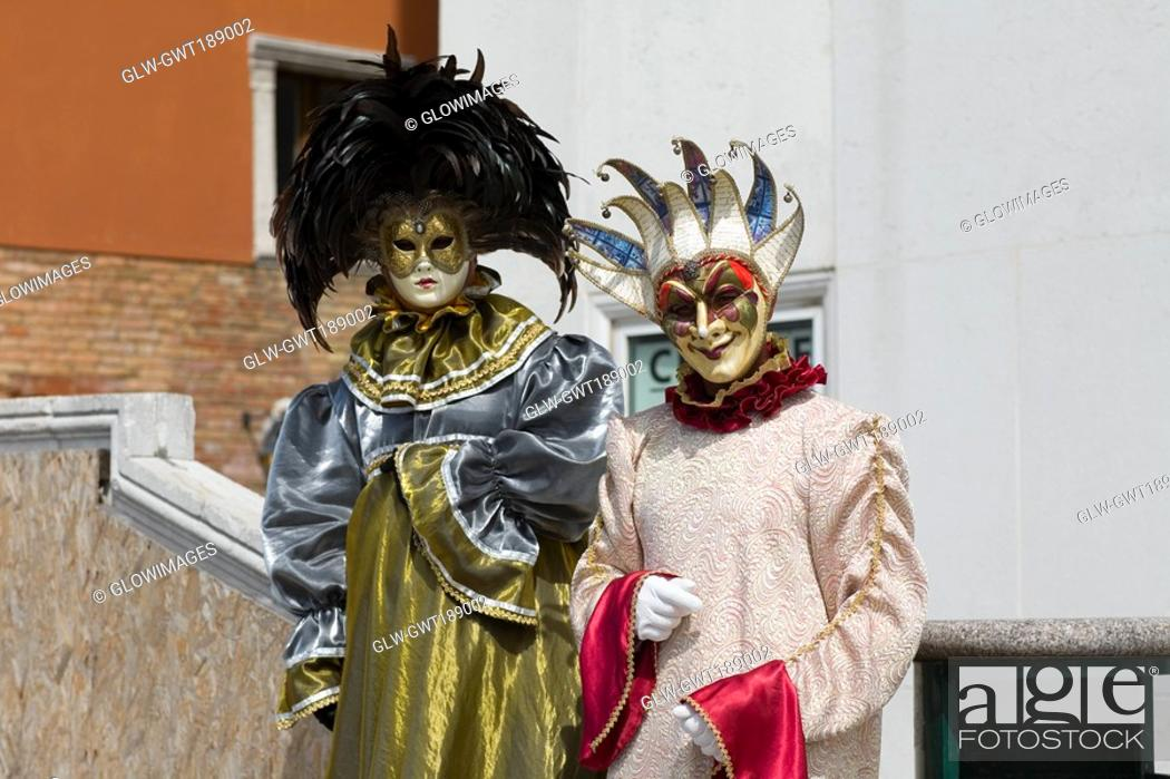 Stock Photo: Close-up of two people wearing masquerade masks, Venice, Italy.