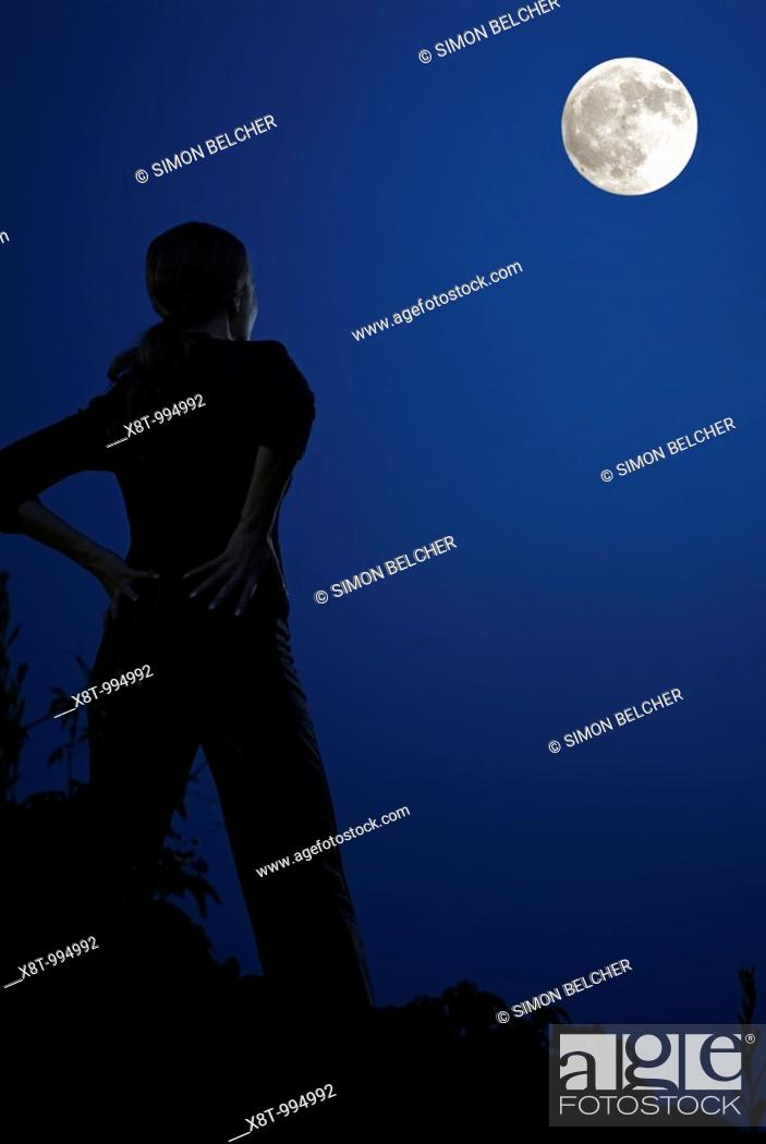 Stock Photo: Woman Standing on a Rocky Outcrop Silhouetted by the Moon.