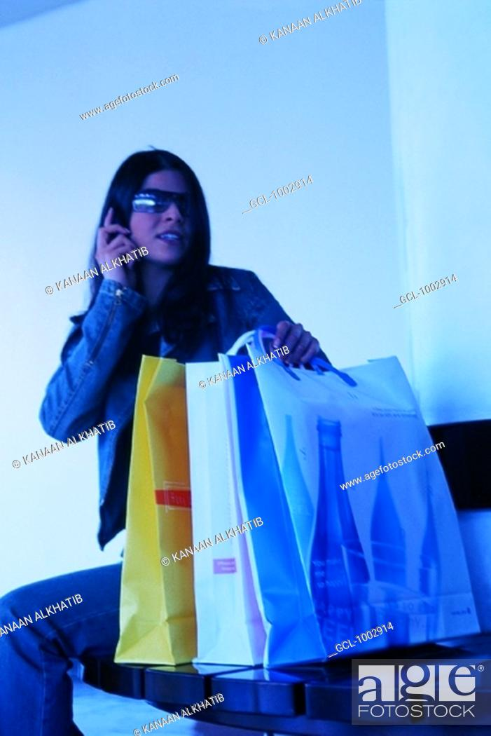 Stock Photo: Woman using mobile phone and holding shopping bags.