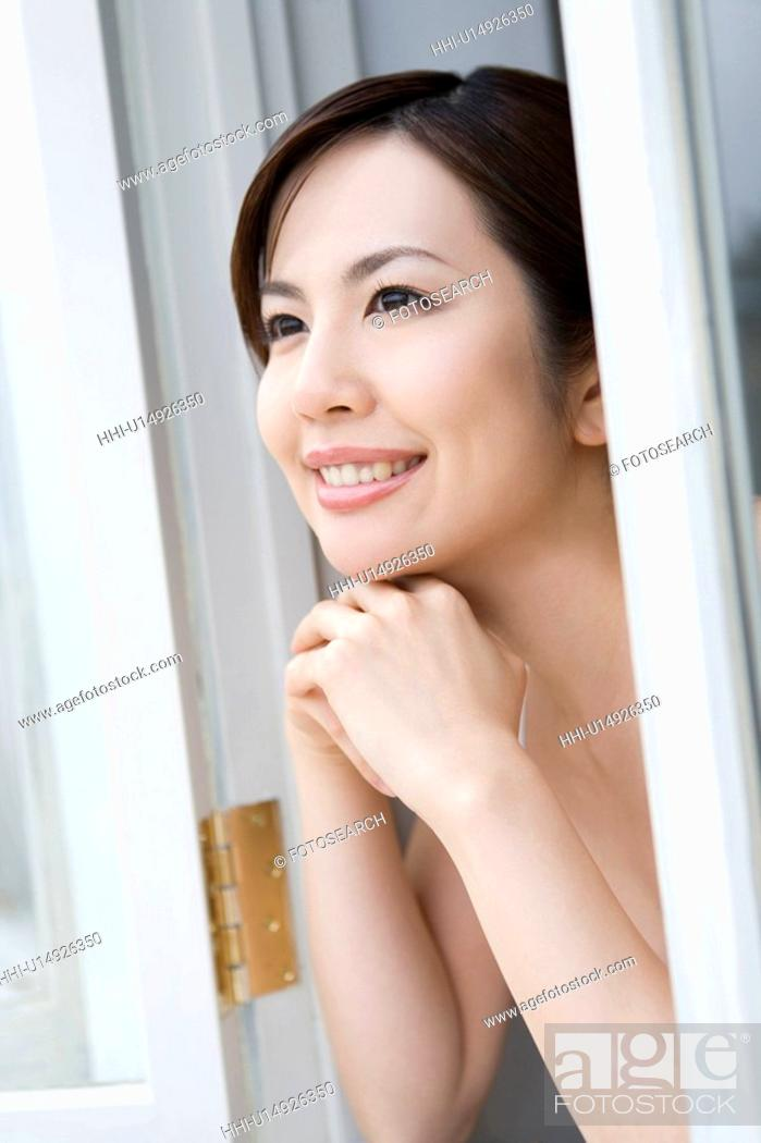 Stock Photo: Young woman with hands under chin, looking out window, side view.
