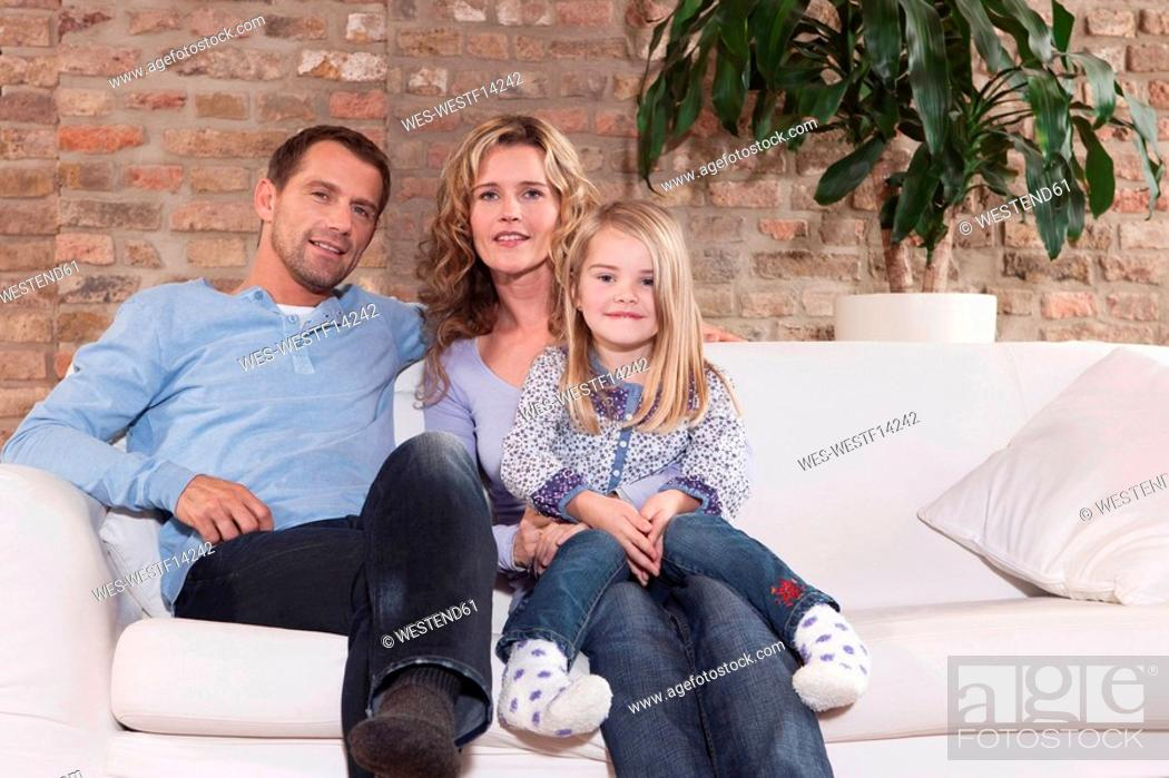 Stock Photo: Germany, Cologne, Family sitting on sofa in living room, smiling, portrait.