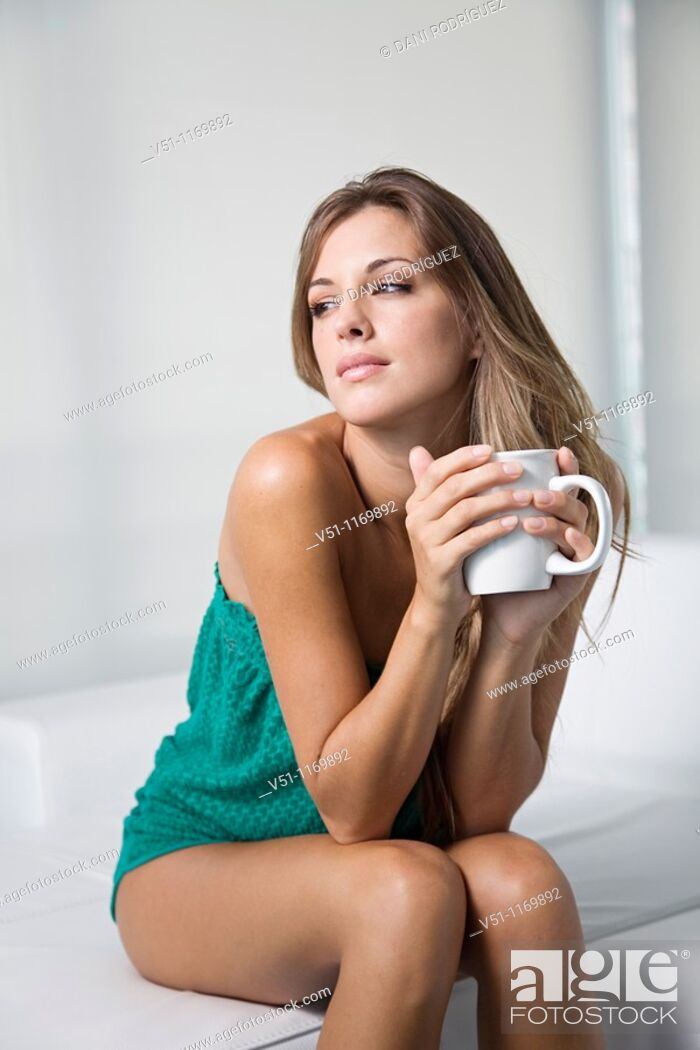 Stock Photo: Beatiful pensive blonde woman enjoying a drink at home.