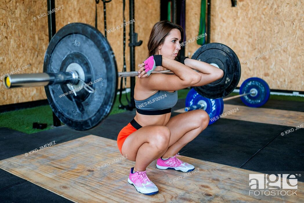 Stock Photo: Woman lifting barbell in gym.