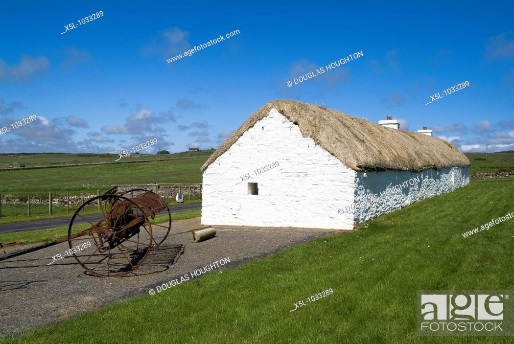 Stock Photo: Laidhay Croft Museum DUNBEATH CAITHNESS Whitewashed thatched ancient longhouse and old farming equipment.