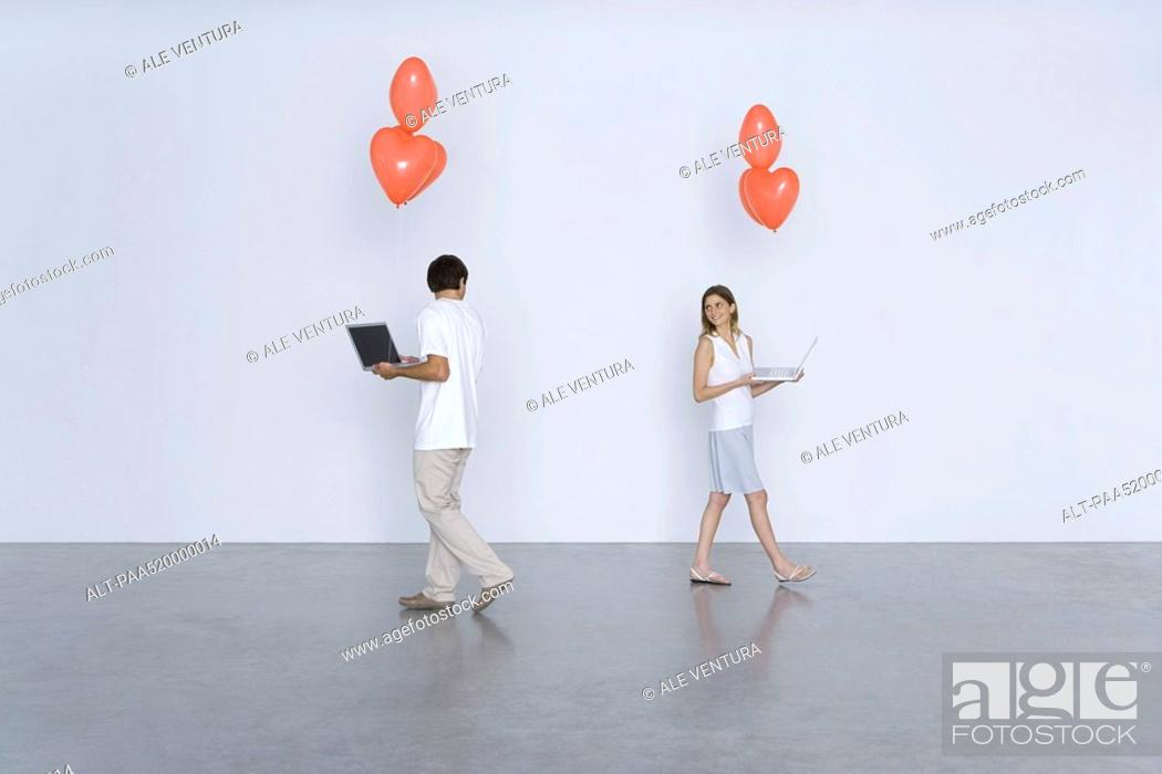 Stock Photo: Man and woman carrying laptop computers and heart balloons, smiling over their shoulders at each other.