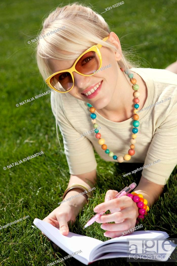 Stock Photo: one young woman reading book on the grass in summer.