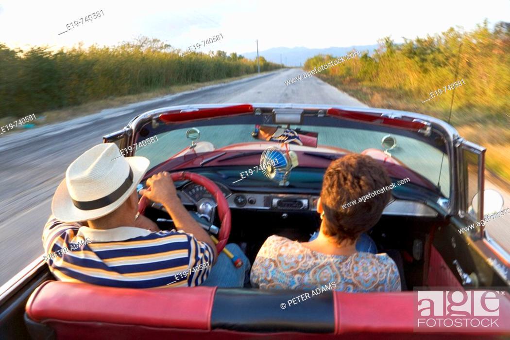 Stock Photo: Couple in 1950 Chevrolet convertible, Cuba.