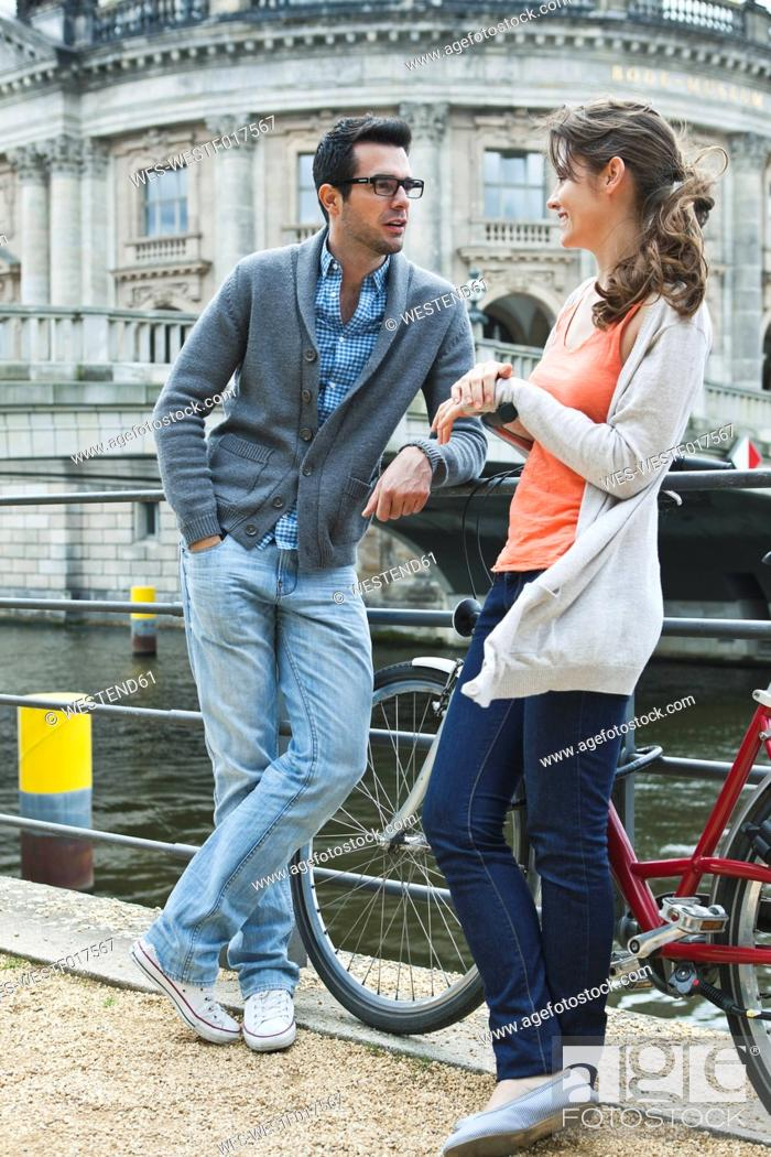 Stock Photo: Germany, Berlin, Couple leaning on fence near river and talking.