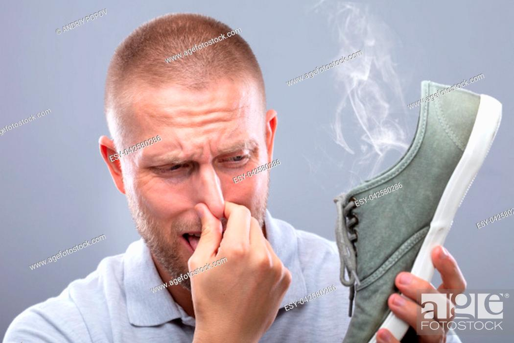 Stock Photo: Close-up Of A Man Covering His Nose While Holding Stinky Shoe On Grey Background.