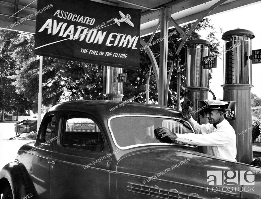 Stock Photo: United States: c. 1938.A gas station attendent cleans a customer's automobile windshield as the car is filled with 19å¢ a gallon gas.