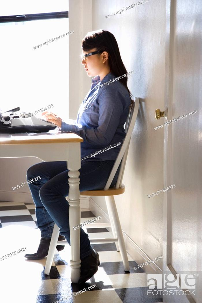 Stock Photo: Pretty young Asian woman sitting in chair typing on typewriter in kitchen.