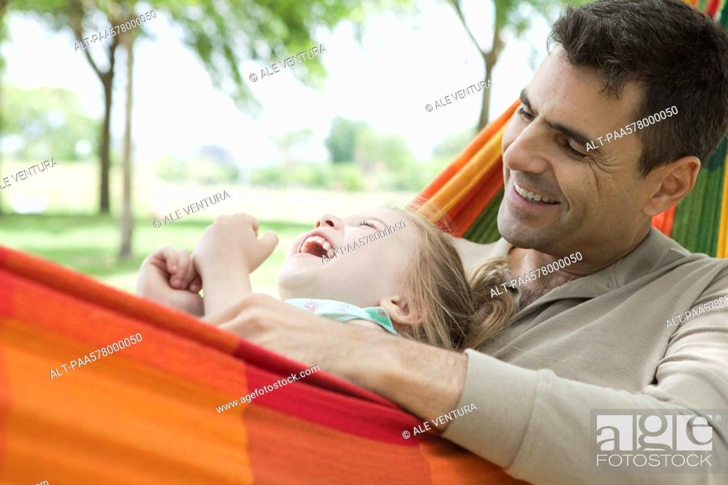 Stock Photo: Father and daughter relaxing together in hammock, both laughing.