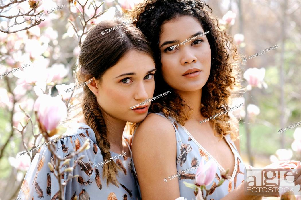 Stock Photo: Loving sisters standing in park during springtime.