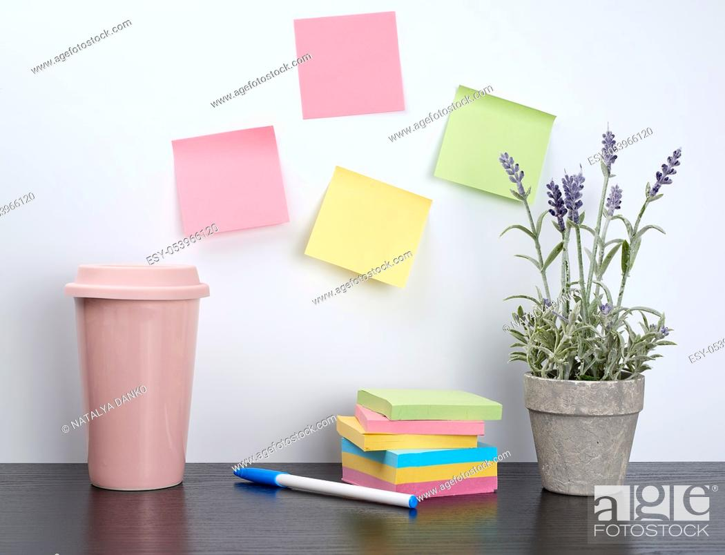 Imagen: stack of spiral notebooks and colored stickers, next to a ceramic pot with a flower on a black table, white wall, Scandinavian-style minimalism.