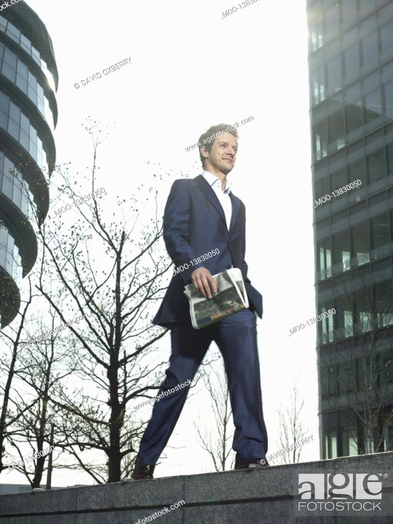 Stock Photo: Young man in suit walking on wall outside office building holding newspaper.
