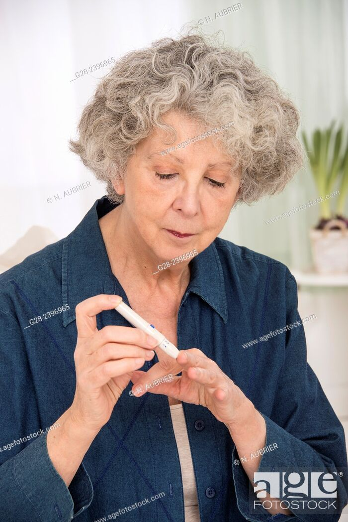 Stock Photo: Beautiful senior woman using an auto blood tester for diabetes on one of her finger at home.