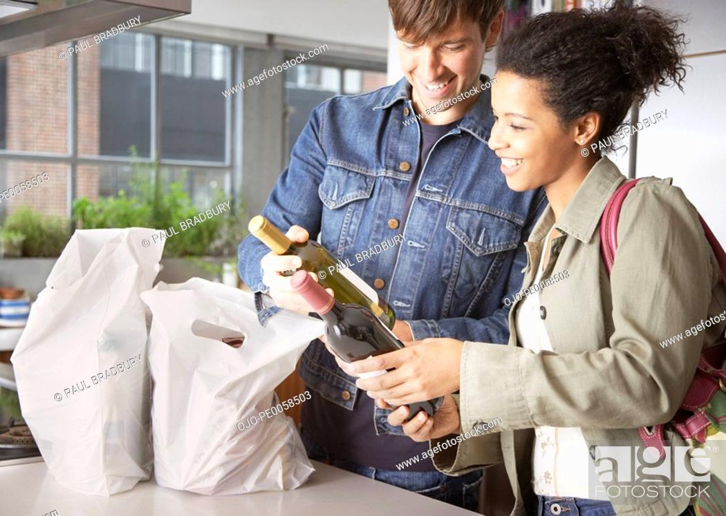 Stock Photo: Couple with groceries and wine in kitchen.