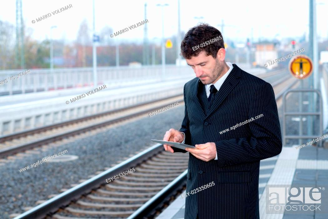 Stock Photo: businessman on railroad station is waiting and using tablet pc.