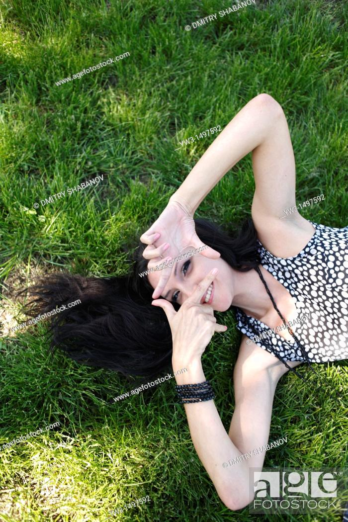 Stock Photo: 25 year old woman outdoors on the grass.