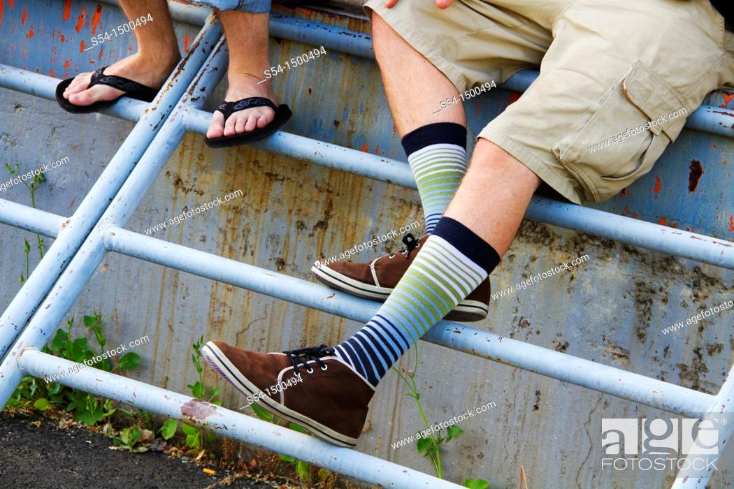 Stock Photo: Two young men, one wearing unusual shoes and socks.