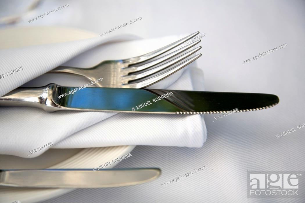 Stock Photo: Table setting of Cutlery wrapped in cloth napkin on plate.