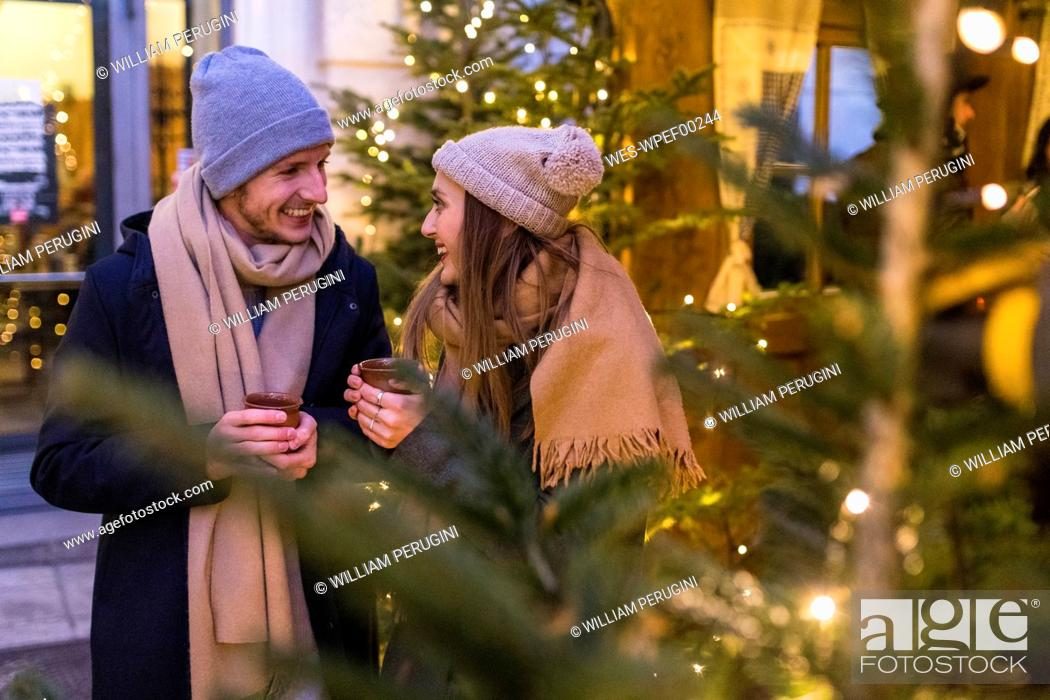 Stock Photo: Happy young couple drinking mulled wine at Christmas market.
