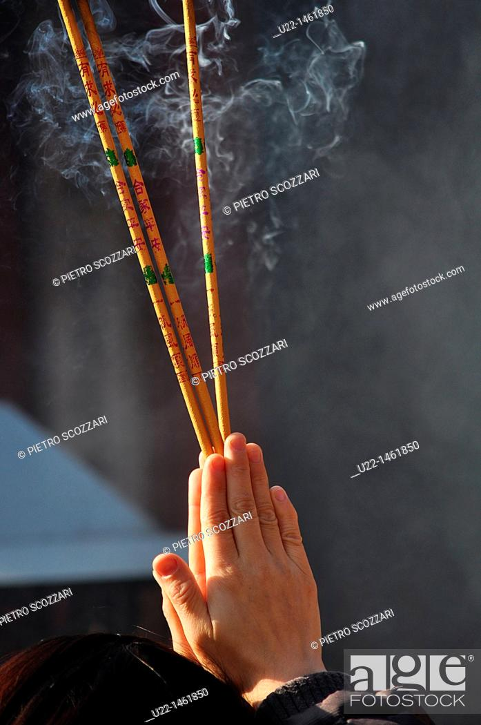 Stock Photo: Beijing (China): a person prays burning incense at the Dongyue Temple during the Spring Festival.