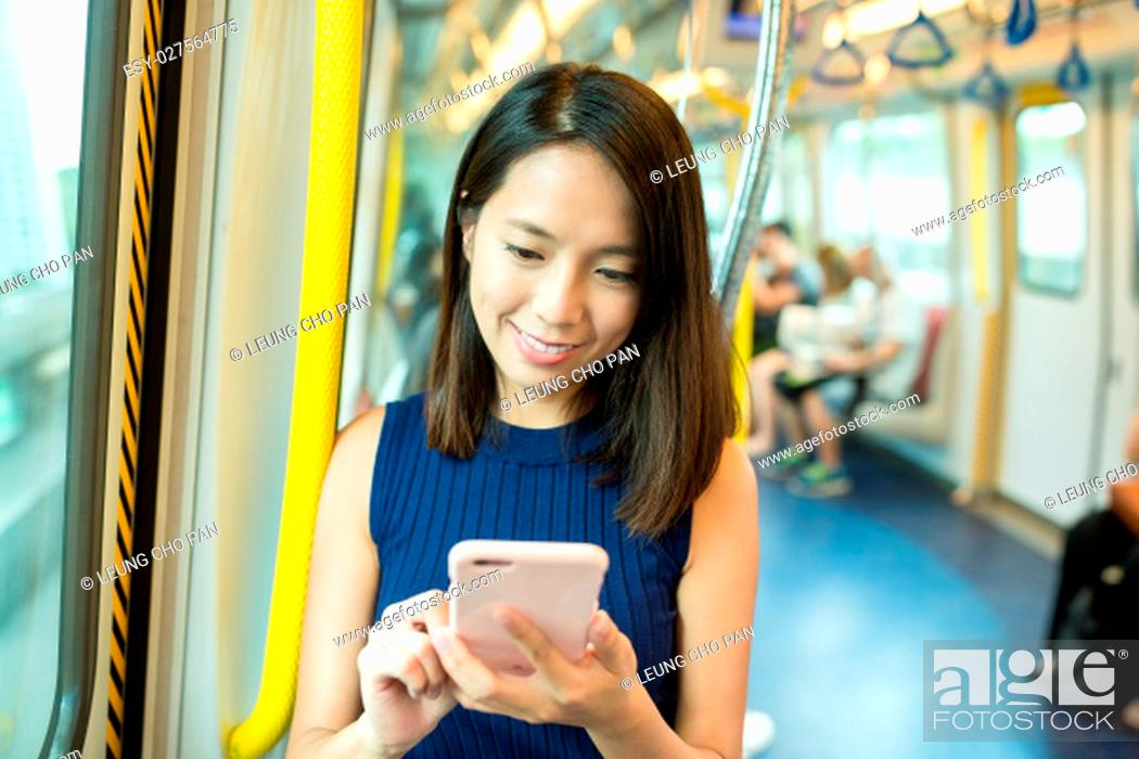 Stock Photo: Woman using cellphone inside train compartment.