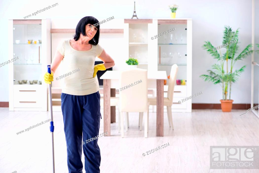 Stock Photo: Old mature woman tired after house chores.