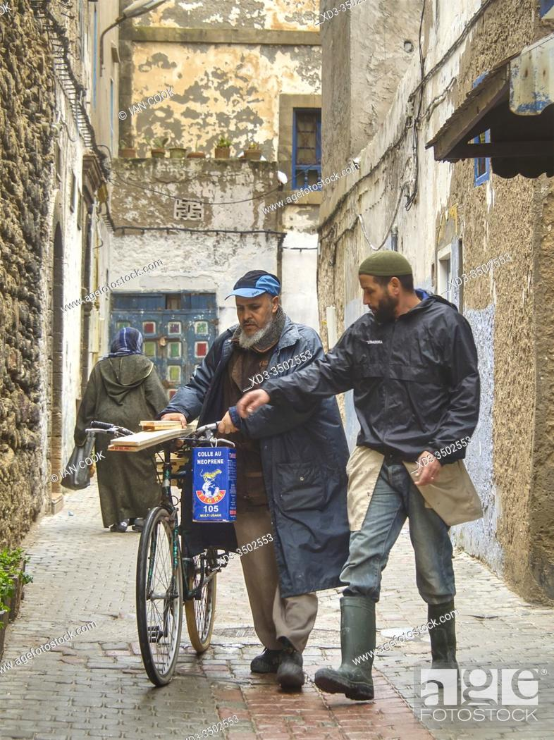 Stock Photo: man with some lumber on his bicycle with a friend, Essaouira, Morocco.